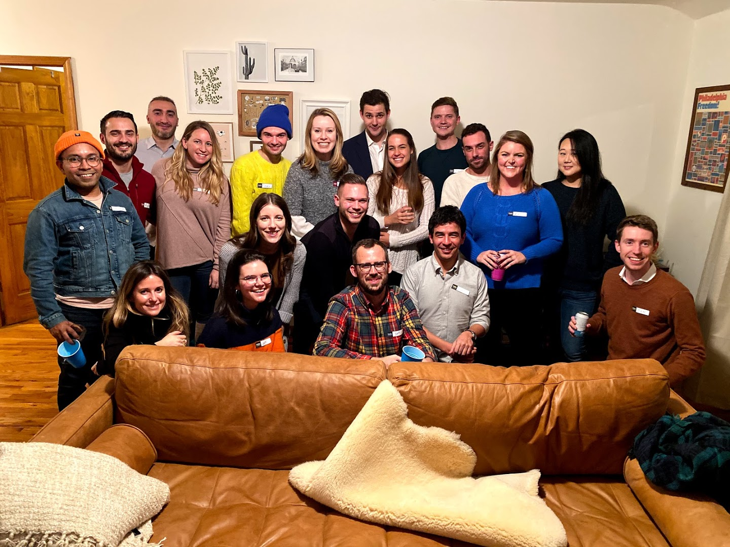 Approx 20 people arranged for a group photo inside an apartment at a house party
